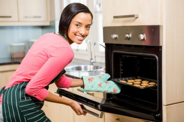 Улыбающаяся женщина печет печенье