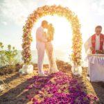 Поцелуй молодоженов под свадебной аркой